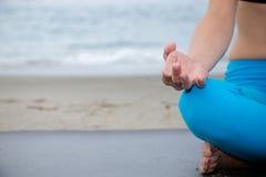Schönheit, die am Strand meditiert Lizenzfreies Stockfoto