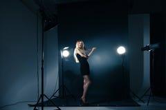 Schönheit, die am Studio in den hellen Blitzen aufwirft Lizenzfreie Stockfotografie