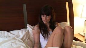 Schönheit, die am Telefon sitzt auf ihrem Bett spricht stock video footage