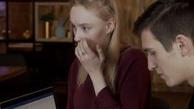Schönheit, die unter jungen Leuten nahe einem Laptop lächelt stock video
