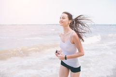 Schönheit, die während des Sonnenuntergangs läuft Junges Eignungsmodell nahe Küste Angekleidet in der Sportkleidung lizenzfreie stockfotos