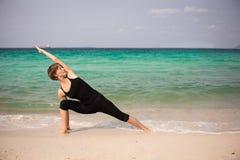 Schönheit, die Yoga auf dem Meer tut Lizenzfreie Stockbilder