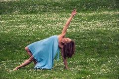 Schönheit, die Yoga auf Wiese tut lizenzfreie stockfotos