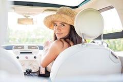 Schönheit, die zurück beim Fahren des Autos schaut Lizenzfreies Stockfoto