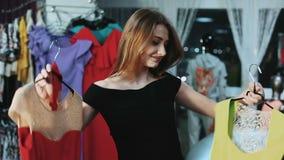 Schönheit, die zwischen zwei Kleidern wählt stock footage