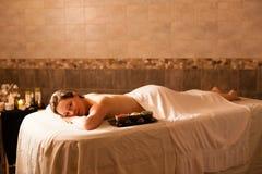 Schönheit in einem Badekurort, der auf einem Massagevorsprung sich entspannt Stockfotos