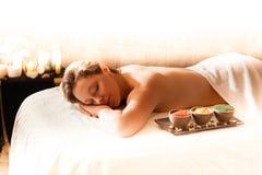 Schönheit in einem Badekurort, der auf einem Massagevorsprung sich entspannt Stockbild