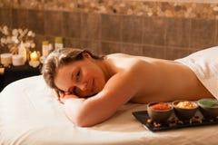Schönheit in einem Badekurort, der auf einem Massagevorsprung sich entspannt Lizenzfreies Stockfoto