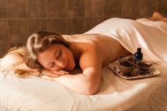 Schönheit in einem Badekurort, der auf einem Massagevorsprung sich entspannt Lizenzfreie Stockbilder