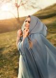 Schönheit in einem blauen Regenmantel lizenzfreie stockfotografie