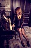 Schönheit in einem eleganten Kleid sitzt am Klavier Sexy Mädchen im Spitzeboudoirkleid und -korsett Sinnlicher Retro- Zauber stockfotografie