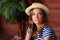 Schönheit in einem gestreiften Hemd und in einem Hut, die auf der Vera sitzen Stockfotos