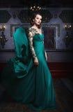 Schönheit in einem grünen langen Kleid auf einem Hintergrund von reich stockfotografie
