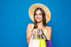 Schönheit in einem Hut in Einkaufsverkäufen der stilvollen Kleidung auf einem blauen Hintergrund, mehrfarbige Taschen stehen auf  Stockfotos
