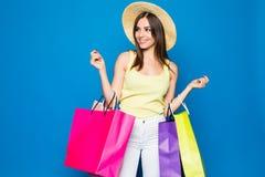 Schönheit in einem Hut in Einkaufsverkäufen der stilvollen Kleidung auf einem blauen Hintergrund, mehrfarbige Taschen stehen auf  Stockfotografie