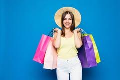 Schönheit in einem Hut in Einkaufsverkäufen der stilvollen Kleidung auf einem blauen Hintergrund, mehrfarbige Taschen stehen auf  Lizenzfreie Stockfotografie