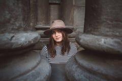 Schönheit in einem Hut und in einem gestreiften Hemd, welche die Kamera betrachten Gl?ckliches junges M?dchen, das Taschen auf ei stockbild