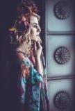 Schönheit in einem Kleid von Blumenfarben mit Kranz von flowe Stockbilder