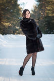 Schönheit in einem Pelzmantel im Winterwald Lizenzfreie Stockbilder