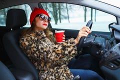 Schönheit in einem Pelzmantel und in einem roten Hut mit Kaffee zum Mitnehmen driv Lizenzfreie Stockfotografie