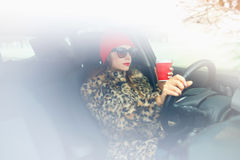 Schönheit in einem Pelzmantel und in einem roten Hut mit Kaffee zum Mitnehmen driv Lizenzfreies Stockbild