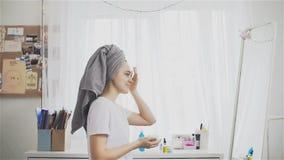 Schönheit in einem Tuch, das Feuchtigkeitscreme auf Gesicht setzt stock footage