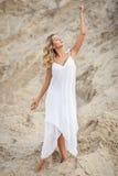 Schönheit in einem weißen Kleid in einer Wüste Stockfotografie