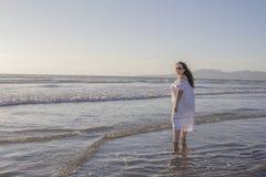 Schönheit in einem weißen Kleid und in der Sonnenbrille das Meerwasser genießend lizenzfreie stockbilder