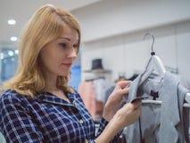 Schönheit in einer Kleidungsboutique Blondes Mädchen wählt Gussnaht Lizenzfreie Stockfotografie
