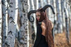 Schönheit gekleidet als feenhafte Hexe im Regenmantel und mit Hörnern für Halloween Lizenzfreies Stockbild