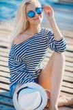 Schönheit in gestreifter Weste auf dem Dock Stockfotos