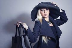 Schönheit im Überzieher und in Hat.Handbag Lizenzfreie Stockbilder