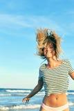 Schönheit im Badeanzug, der nahe dem Meer springt Lizenzfreies Stockfoto