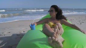 Schönheit im Bikini entspannt sich am Seestrand hält Cocktail in der Hand und schaut weg stock video footage