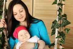 Schönheit im Blau mit lächelndem Baby auf Schwingen Stockfoto