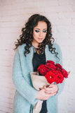 Schönheit im blauen Mantel mit roten Rosen im Kraftpapier Lizenzfreie Stockfotos