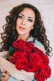 Schönheit im blauen Mantel mit roten Rosen im Kraftpapier Lizenzfreies Stockfoto