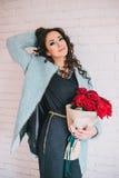Schönheit im blauen Mantel mit roten Rosen im Kraftpapier Lizenzfreie Stockfotografie