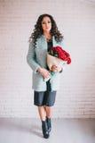 Schönheit im blauen Mantel mit roten Rosen im Kraftpapier Stockfotografie