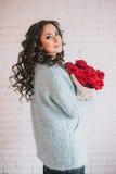 Schönheit im blauen Mantel mit roten Rosen im Kraftpapier Lizenzfreie Stockbilder