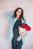 Schönheit im blauen Mantel mit roten Rosen im Kraftpapier Stockbild