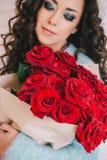 Schönheit im blauen Mantel mit roten Rosen im Kraftpapier Stockfotos