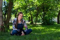 Schönheit im Denimgesamtsitzen auf dem grünen Gras im Park lizenzfreies stockfoto