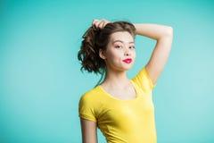 Schönheit im gelben T-Shirt, welches die Kamera betrachtet lizenzfreies stockbild