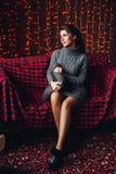 Schönheit im grauen Strickkleid mit dem langen Haar im Endstück auf gemütlichem überprüftem Sofa gegen Girlande lizenzfreie stockbilder