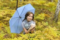 Schönheit im Herbstwald mit blauem Regenschirm lizenzfreies stockbild