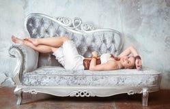 Schönheit im Korsett und in der Hose auf dem Sofa lizenzfreies stockfoto