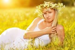 Schönheit im Kranz von Blumen liegt im grünen Gras heraus Lizenzfreie Stockfotos