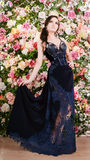 Schönheit im langen blauen Spitzekleid auf Blumenhintergrund Art und Weise Lizenzfreies Stockbild