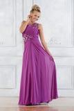 Schönheit im lila langen Kleid im weißen Innenraum. lizenzfreie stockfotos